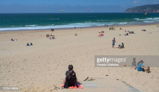 Kite surfers are seen in the background while beachgoers keep social distancing in Praia do Guincho during the COVID19 Coronavirus pandemic on May 17...