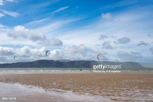 kite surfers at conwy sands, llandudno, north wales - gwynedd stock photos and pictures