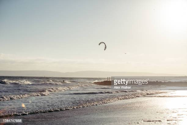 kite surfers in waves at sunset - プール市 ストックフォトと画像
