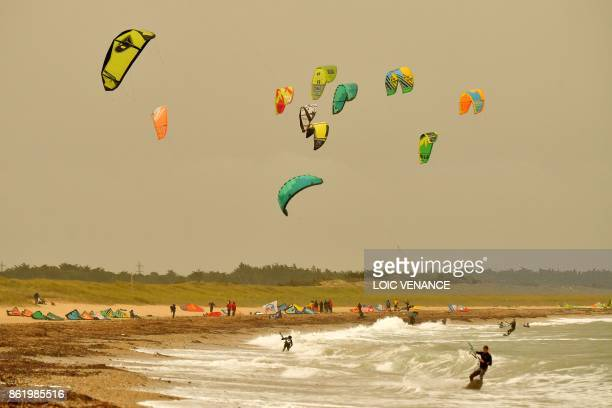 TOPSHOT Kite surfers surf on October 16 2017 in Quiberon western France as the sky turned a yellowochre colour due to sand from the Sahara desert and...