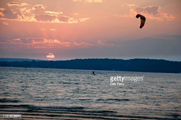 kiteboarding against the sunset - traverse city fotografías e imágenes de stock