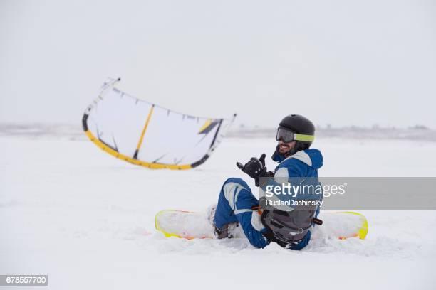 Kiter showing hang loose sign. Snowboarder kiting on snow at winter.