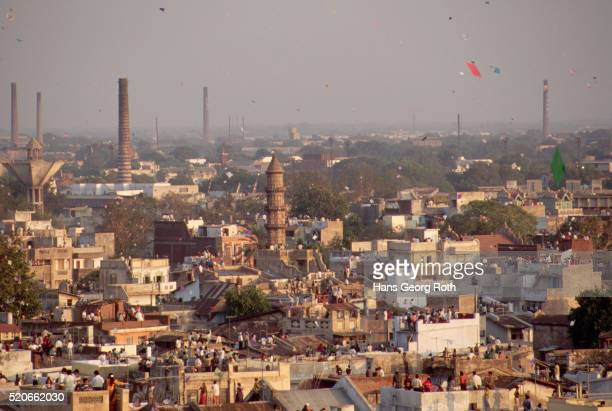 kites fly over indian rooftops - ahmedabad stock pictures, royalty-free photos & images