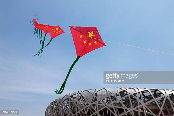 kites flying by the beijing national stadium - stadio olimpico nazionale foto e immagini stock