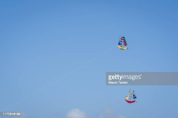 kites in the clear sky of bali - mauro tandoi stock pictures, royalty-free photos & images