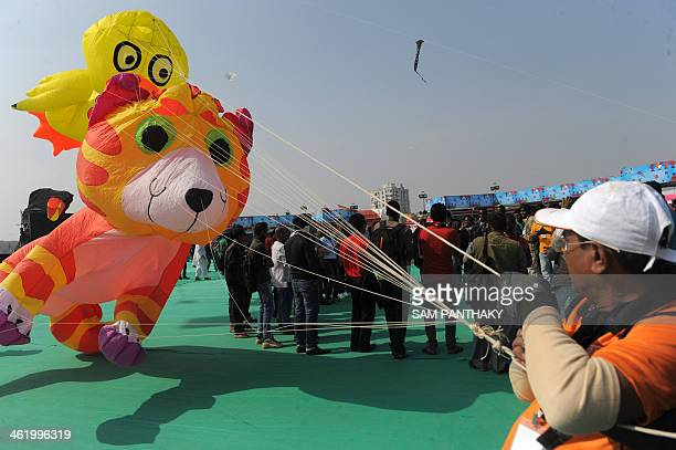 Kites take to the sky during the International Kite Festival in Ahmedabad on January 12 2014 Gujarat state Chief Minister Narendra Modi inaugurated...