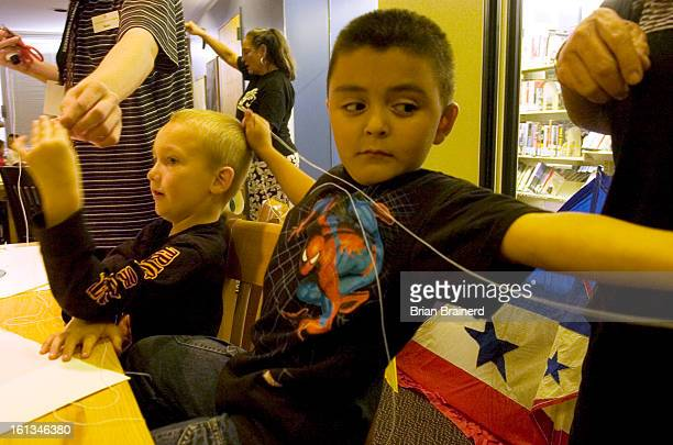 kites10a Michael Lynn Baugh left and Eric Martinez both age 6 measure string for a kite bridle while participating in the Athmar Park Library's After...