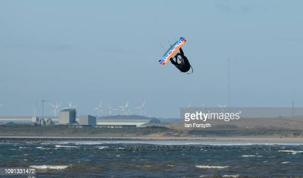 A kitesurfer gets some air as he enjoys surfing in strong onshore winds at South Gare against the industrial backdrop of Hartlepool on January 8 2019...