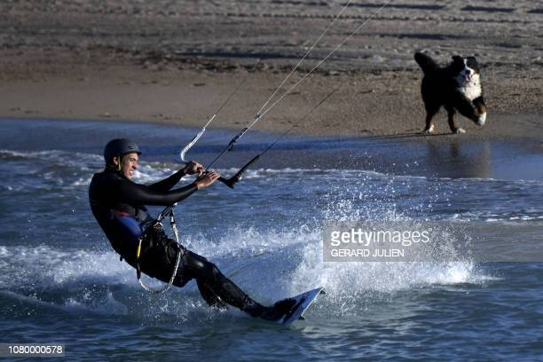 A kitesurfer is watched by a dog as he practices in the Mediterranean Sea off Marseille southern France on January 10 2019