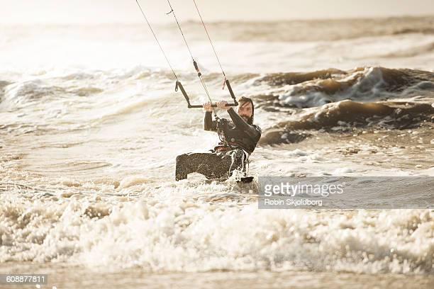 Kitesurfer riding white water waves