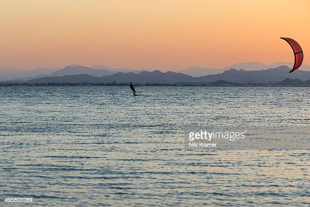 Kitesurfer, surfing on the blue lagoon of Ras Al Hadd Lagoon in the evening light, Ras Al Hadd, Ash Sharqiyah, Oman