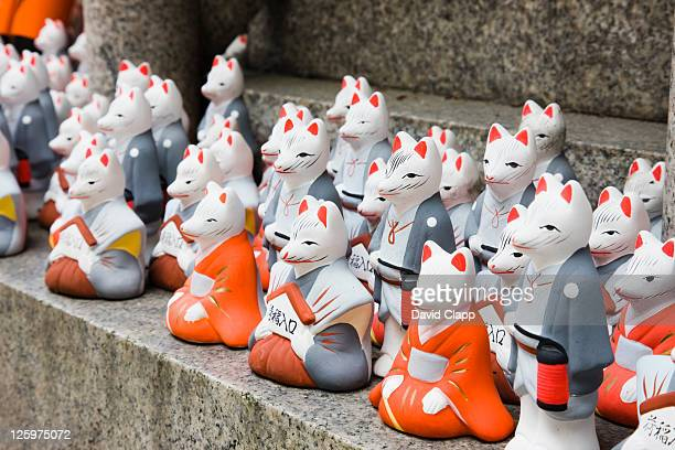 Kitsune or messenger foxes that are a symbol of wealth in Fushimi Inari Shrine, Kyoto, Japan
