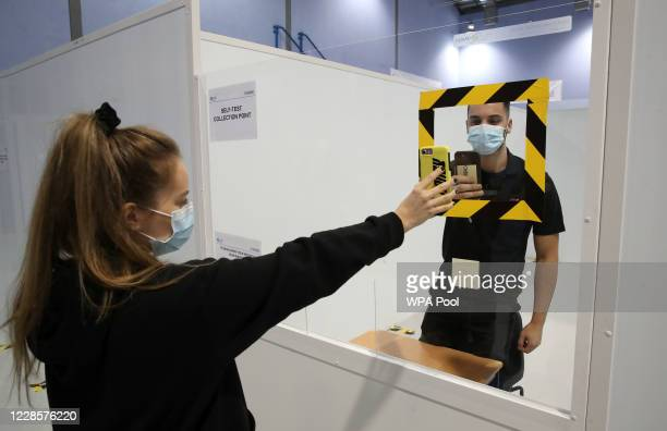 Kitty Ritchie has her QR code scanned on entry as she demonstrates how to take a coronavirus test at a new walkthrough testing centre which will open...