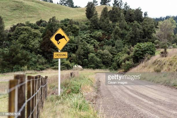 kiwi crossing sign next to fence near a gravel road in new zealand - ホークスベイ地域 ストックフォトと画像