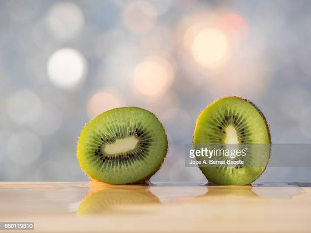 kiwi fruit,  divide  for the half, illuminated by the light of the sun - partido político stock photos and pictures