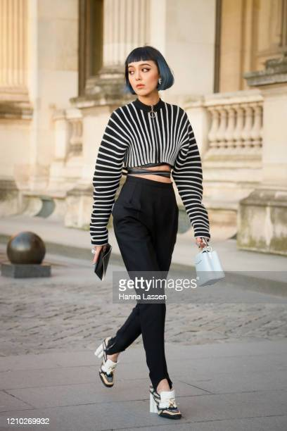 Kiwi Lee wearing Louis Vuitton black and white top, black pants, white bag and white leather shoes outside the Louis Vuitton show during Paris...