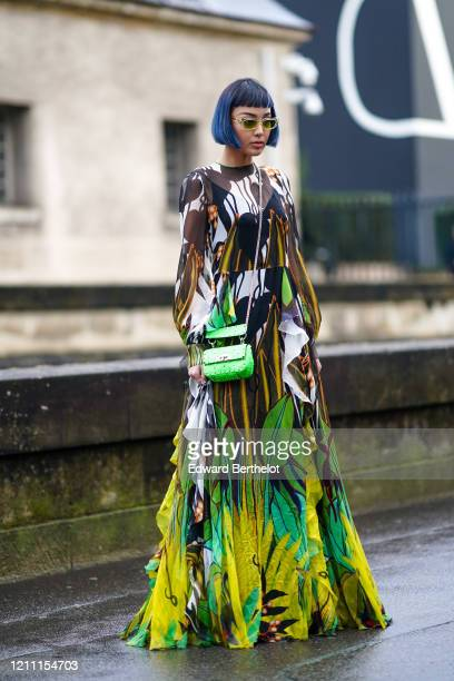 Kiwi Lee wears a pleated and ruffled long colored floral print dress, a neon green studded bag, sunglasses, outside Valentino, during Paris Fashion...