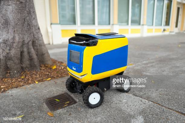 Kiwi self driving autonomous package delivery robot parked on a street corner on Shattuck Avenue in Berkeley, California, August 21, 2018.