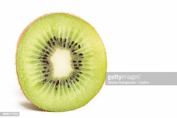 kiwi slice against white background - tropical fruit stock pictures, royalty-free photos & images