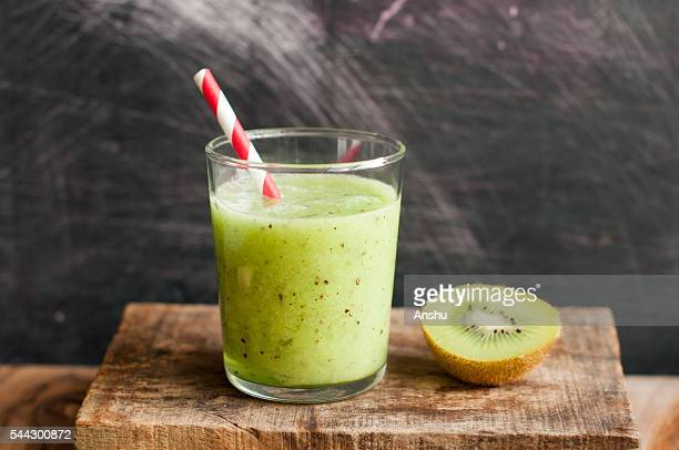 Kiwi smoothie on a wooden background with paper straw