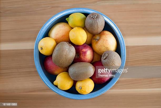 Kiwis, apples and lemons in a bowl