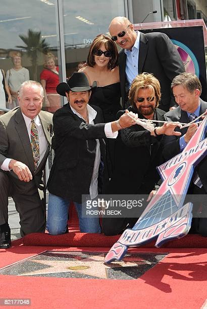 Kix Brooks and Ronnie Dunn of the country music duo Brooks Dunn are joined by Dr Phil McGraw and his wife Robin McGraw and other dignitaries as they...