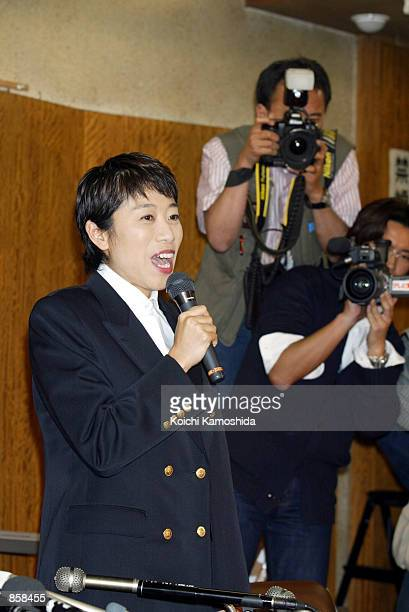 Kiyomi Tsujimoto an opposition Social Democratic Party lawmaker removes her lawmaker's pin from her lapel during a news conference at the SDP...