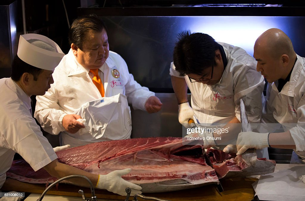 Kiyomura Co. President Kiyoshi Kimura, center left, looks at an employee cutting a fresh bluefin tuna inside one of the company's Sushi Zanmai sushi restaurants after the year's first auction at Tsukiji Market on January 5, 2017 in Tokyo, Japan. Kiyomura Co. bid the highest priced tuna weighing 212 kilogram (467.38 pound) for 74.2 million yen ($637,155) at the year's first auction.