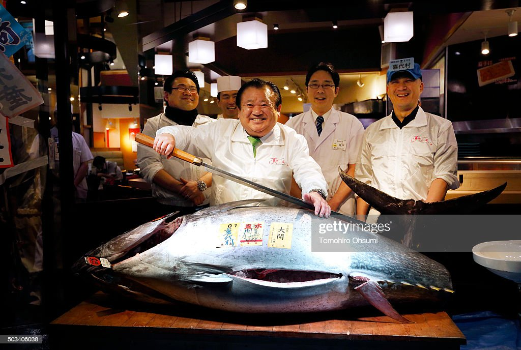 Kiyomura K.K. President Kiyoshi Kimura, center, poses with a fresh bluefin tuna in front of one of the company's Sushi Zanmai sushi restaurants after the year's first auction at Tsukiji Market on January 5, 2016 in Tokyo, Japan. Kiyomura K.K., which operates the Sushi Zanmai sushi restaurant chain, bid the highest priced tuna weighing 200 kilogram (441 pound) for 14 million yen ($117,306) at the year's first auction.