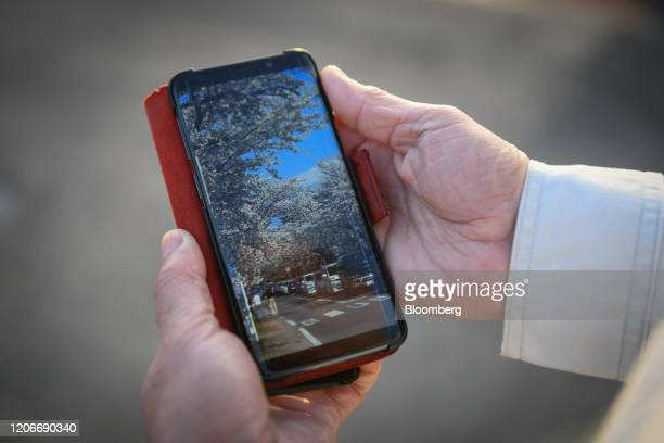 Kiyonori Watanabe director of Fukushima Electric Power Co holds his smartphone displaying an image of cherry blossoms in the Yonomori neighborhood of...