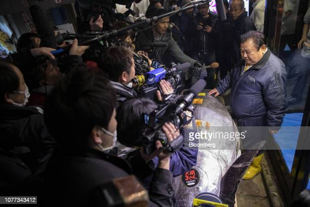 Kiyoshi Kimura president of Kiyomura Corp stands with a newlypurchased tuna as he speaks with members of the media in front of a Sushizanmai...