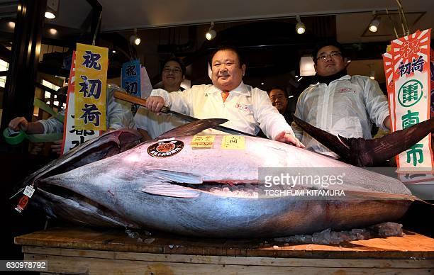 Kiyoshi Kimura president of sushi restaurant chain SushiZanmaiposes with a 212kilogram bluefin tuna at his main restaurant near the Tsukiji fish...