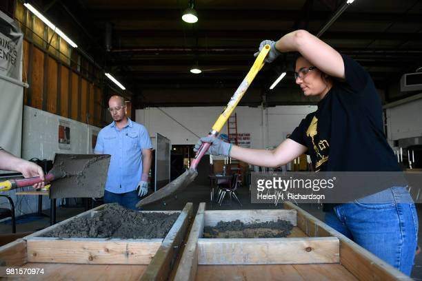 Kj Farmer right uses a shovel to pour concrete into forms as she takes part in the Construction Careers Now program at the Central 70 Neighborhood...