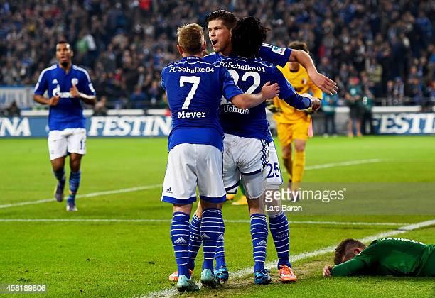 Klaas Jan Huntelaar of Schalke 04 celebrates with Atsuto Uchida of Schalke 04 and Max Meyer of Schalke 04 after scoring his teams first goal during...