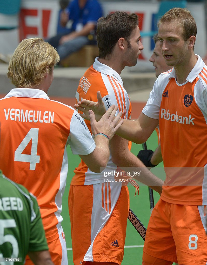 Klaas Vermeulen of the Netherlands (L) congratulates teammate Billy Bakker (R) after he scored against Pakistan during their semifinal at the men's Hockey Champions Trophy tournament in Melbourne on December 8, 2012. IMAGE STRICTLY RESTRICTED TO EDITORIAL USE - STRICTLY NO COMMERCIAL USE AFP PHOTO / Paul CROCK