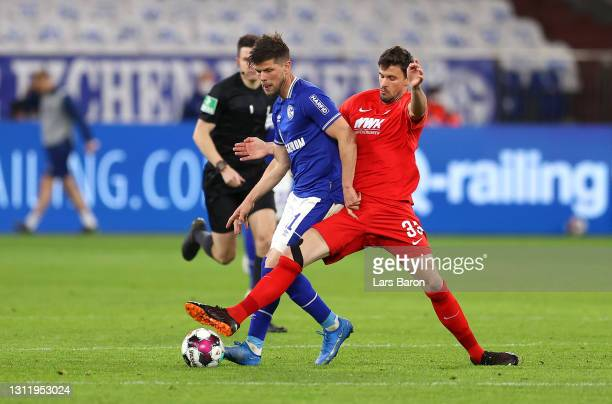 Klaas-Jan Huntelaar of FC Schalke 04 is challenged by Tobias Strobl of FC Augsburg during the Bundesliga match between FC Schalke 04 and FC Augsburg...