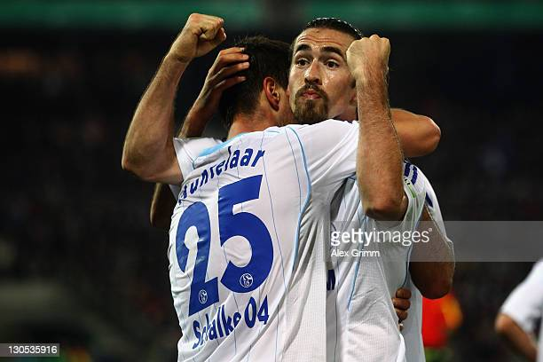 Klaas-Jan Huntelaar of Schalke celebrates his team's first goal with team mate Christian Fuchs during the DFB Cup second round match between...