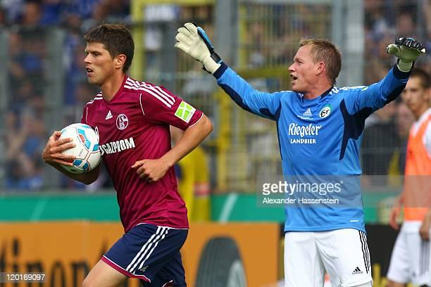 Klaas-Jan Huntelaar of Schalke celebrates scoring the 8th team goal whilst Alexander Ernst keeper of Teningen reacts during the DFB Pokal first round...