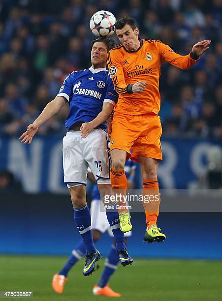 KlaasJan Huntelaar of Schalke jumps for a header with Gareth Bale of Madrid during the UEFA Champions League Round of 16 first leg match between FC...