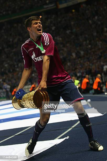 KlaasJan Huntelaar of Schalke lifts the DFB Cup trophy following his team's victory at the end of the the DFB Cup final match between MSV Duisburg...