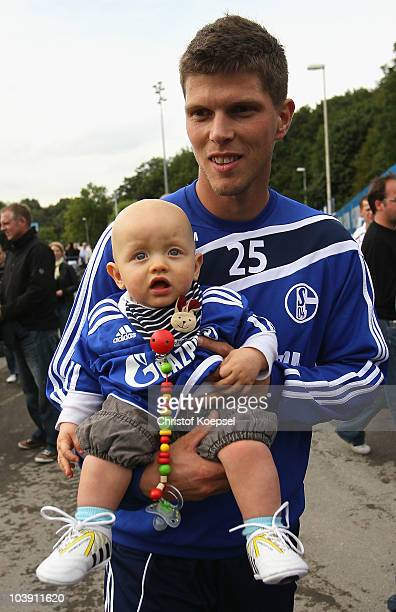 KlaasJan Huntelaar poses with a baby during the FC Schalke training session at the training ground on September 8 2010 in Gelsenkirchen Germany