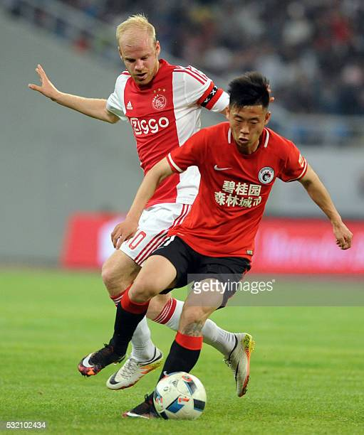 Klaassen Davy of Ajax Amsterdam fights for the ball with Liu Shangkun of Chinese Super League club Liaoning Whowin FC during their friendly match in...