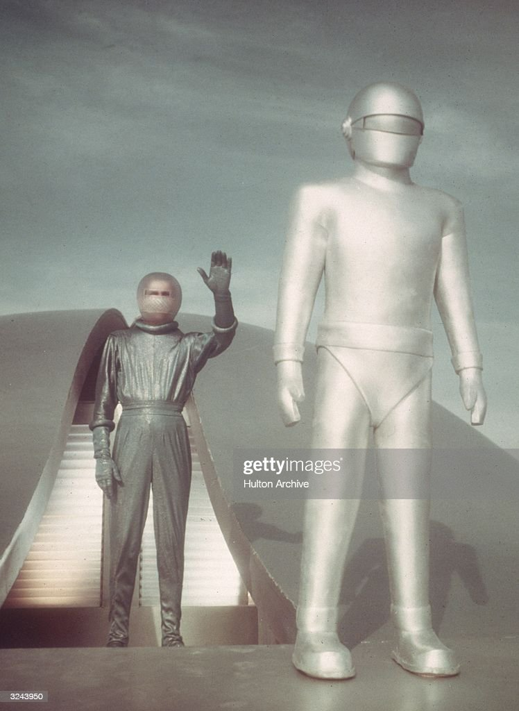 Klaatu the alien, played by actor Michael Rennie (1909 - 1971), and Gort the robot, played by Lock Martin (1916 - 1959), emerge from their spacecraft to warn humans of impending nuclear disaster in a promotional still from the film, 'The Day The Earth Stood Still'.