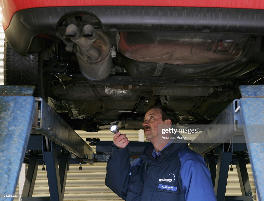 F. Klante, inspector of the Technical Supervisory Association (T?V), checks the underneath of a passenger car on February 8, 2007 in Berlin, Germany. The European Commission announced new carbon dioxide (CO2) targets for car makers which the European Automobile Manufacturers Association (ACEA) said it could not agree with, stating they are 'unbalanced and damaging to the European economy in terms of wealth, employment and growth potential.'