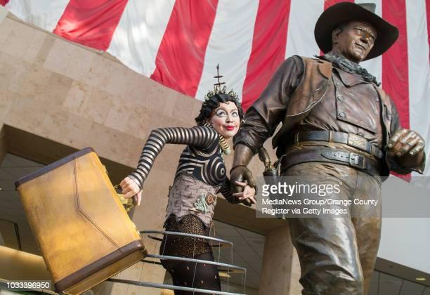 Klara the Telegraph of the Invisible a character from Cirque du Soleil's Kurios holds the hand of the John Wayne statue at John Wayne Airport Kurios...