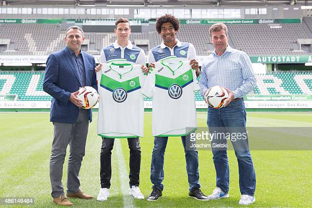 Klaus Allofs, Julian Draxler, Dante and Head Coach Dieter Hecking pose for photos on the pitch during a press conference at Volkswagen Arena on...