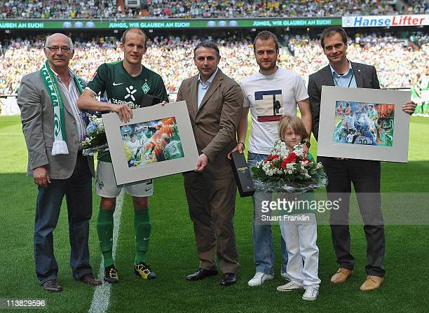 Klaus Allofs sport director of Bremen makes a presentation to Petri Pasanen and Daniel Jansen at the start of the Bundesliga match between SV Werder...