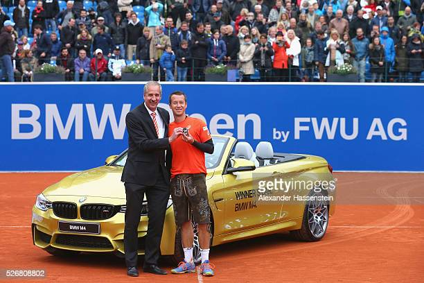 Klaus Draeger board member of BMW group hands over the winners car a BMW M4 cabrio to Philipp Kohlschreiber of Germany after winning his finale match...