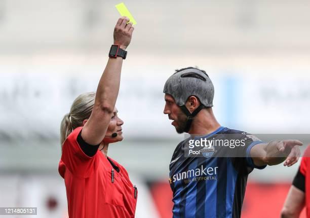 Klaus Gjasula of SC Paderborn 07 is shown a yellow card by referee Bibiana Steinhaus during the Bundesliga match between SC Paderborn 07 and TSG 1899...