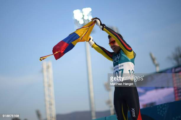 Klaus Jungbluth Rodriguez of Ecuador holds his countries flag after crossing the finish line during the CrossCountry Skiing Men's 15km Free at...